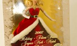 """2007 Holiday Barbie Collectible   2007 Holiday Barbie was the """"Miss Claus"""" Barbie. She is wearing a red velvet strapless gown with a full skirt. It is trimmed with white fur and she has a black belt trimmed in crystals - just like Santa's suit, except"""