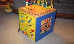 Four sided wooden activity cube with Xs & Os, magnetic wheel, peg sliders and wheel ladder, all topped with shapes on wires. Loads of fun. Solid, durable, colorful, excellent condition. Smoke-free home.