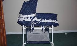 Avalon Bassinet blue & white with teddy bears. Can rock or stay still with or without wheels for easy moving room to room, has basket under to put whatever you wish. Clean and lightly used. Comes with 3 bassinet fitted sheet for the mattress. Willing to