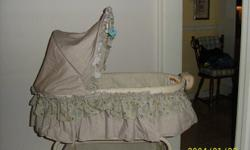 BASSINET - bought new in Dec. 2010-used for approx 5 months.Cream colored. Very clean, from smoke free home, in excellent condition. It has a detactable basket on the base to hold diapers, blankets, clothes etc. Bassinet detaches from stand which is on