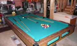 8 foot Brunswick pool table with ball return. Comes with 4 cues, rake, set of balls and a wall mounted cue holder.