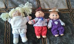 3 cute little Cabbage Patch Dolls. The bigger one is soft bodied, the other two are plastic. Adult owned. Display only. Found an extra little outfit that goes with the bigger doll. About 2-4 inches big.