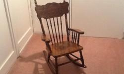 Antique child's rocking chair from Bass River Nova Scotia. Embossed solid wood back with spindles. Embossed Gryphon design on veneer over solid wood seat. Seat height is 11 inches. Veneer seat has some separation and splits, otherwise is in good
