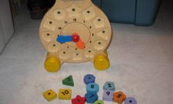 Magnetic, shape clock on wheels. The hands move and the numbers are different magntic shapes.