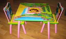 Dora the Explorer wooden table for sale. Comes with 2 chairs. In ok condition. There are a few scratches from use. The middle section lifts up for hidden storage. Asking $25