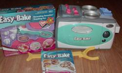 For sale, Easy Bake Oven & Snack Center With An Easy Bake Decorating Sensation Frosting Pen. The Oven Is in the original packaging, was only used a few times and includes: Oven, Yellow Cake Mix, Chocolate Frosting Mix, 1 Pretzel Mix, 2 Baking Pans, 2