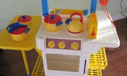 Older Fisher Price kitchen in good shape. Front is stove and oven - other side fridge and sink. Pots and pans and a variety of plastic food, fruit, vegetables and cutlery.