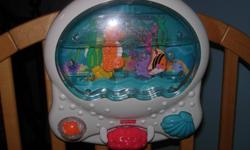 Aquarium that attaches to the side of a crib. -lights, music and fish swim in it...all working...also buttons and things for baby to play with to activate it. -no remote, as this is an older style version, but is in great shape...no scratches, stickers