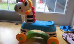 This Zebra sings several songs and makes sound effects when you roll the yellow wheel on it's head. The orange wheels on the bottom don't roll at all, even though they claimed to on the box! Okay for a younger child to sit on, although my son still pushed