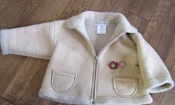 This jacket is so cute and easy to put on!  Manufacturer's name:  Krickets Elite (Made in Canada)   It is tan in colour and features burgundy and green flowers coming from the front pocket.  It has a lamb-skin style interior that wears well and looks
