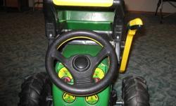 Children's John Deere Riding Tractor in  good condition.