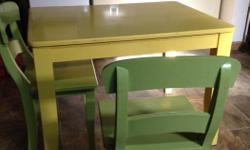 Kid-sized yellow wooden table with three green chairs. Great for crafts and snacks for little ones.