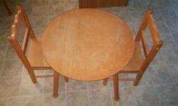"Good condition wooden table and 2 chairs for children. Table is about 18"" high. Chair backs are about 24"" high. Table diameter is about 24""."