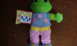 """A singing frog that educates on colours, shapes and numbers, depending on what you're looking for. It sings english/french.   Lily Frog sings and counts all the items in the book that she holds. She sings """"Hi, i'm Lily and you can count on me."""" She then"""