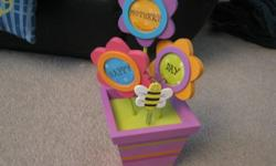 For sale a new flower pot decoration that holds 3 round pictures.