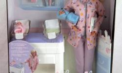 NEW in never opened box Doctor Barbie wears a pink smock done up in a very cute stork pattern, along with matching pink pants and the obligatory white shoes. Her office is nicely outfitted. It includes an exam table with two cradles, bottles, tiny baby
