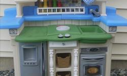 Step 2 Lifestyle Partytime kitchen. Indoor kept (taken outside just for the photos), has phone, blubbling light up stove, microwave. Comes with 3 baskets of food/kitchen stuff (in photo). Excellent condition. Cross posted. Cinnabar Valley