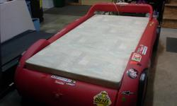 See pic. This bed is a twin size with relatively new memory foam mattress (that cost $250). It has a lighted headboard and storage compartment under the foot of the bed. It is in great shape with racing type decals (removable if desired).