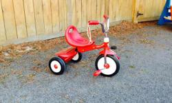 Red 'Radio flyer' red tricycle in excellent condition (barely used). High-quality sturdy steel construction and adjustable seat ensure your child will enjoy the trike for years. Plus, it comes with streamers and a fun covered storage bin. Great for ages
