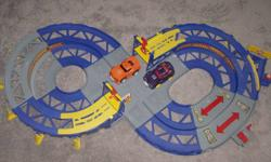 Figure 8 track and 2 cars.  Shake cars and they rev up, let them go and they drive until they crash, can be used on track or bare floor (batteries not included) Track comes apart and has a large Toys R Us cotton bag for storage/transportation.  Great deal