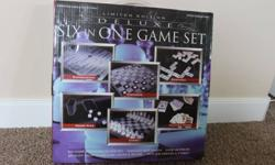 This limited edition Six in One Game Set is new in the box. It has glass game boards and includes the following: backgammon, checkers, mini dominoes, playing cards, chess, and poker dice. It is not designed for children. The same set is listed on