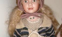 These two dolls are very life like and they are porcelain. The first doll in the first pic has a brownish dress and hat on, and a green sweater and is holding a rabbit, the next doll in the second pic has a sort of orange'y brown hat and sweater, green