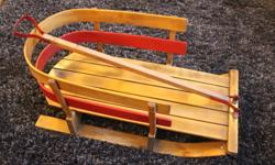 Vintage wooden baby sled with cushion.