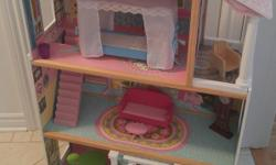 Big dollhouse accommodating easily Barbie sized dolls on 3 levels. Furniture includes bed, terrace chair, kitchen table with 2 chairs, couch, bathtub, clock, and trash can. Maison de poupées assez grande pour bien accommoder des Barbies sur ses 3 étages.