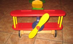 "A wooden ""ride-on"" airplane in bright colors. This toy is perfect for a young child. It has a spinning propeller, a moving rutter in back and the steering wheel turns. The back wheels are coaster type wheels and front wheels are wood w/ rubber tires."
