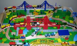 """Wooden train set and 48"""" x 32"""" table.  Lots of track, some Thomas the train items, a battery-operated remote controlles bridge with sound that rises and lowers.  Two drawers to store all your track and rolling stock.  Makes a great Christmas gift."""